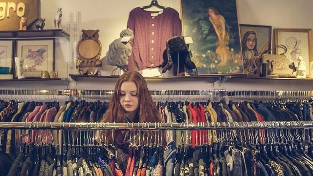 момиче в магазин , разглеждащо дрехи