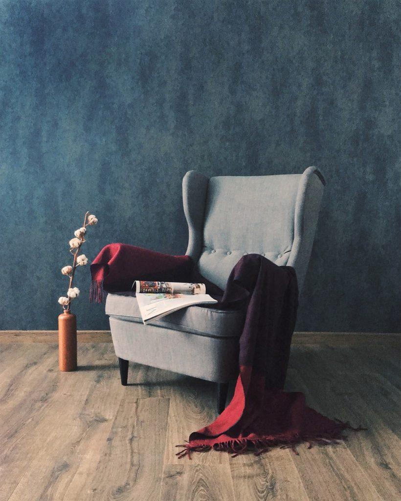 кресло, върху което е посатвено списание и червено одеало